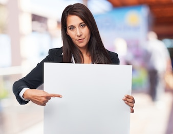 Elegant woman pointing a blank poster