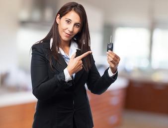 Elegant woman pointing the keys of a car