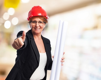 Elegant woman with blueprints and thumb up