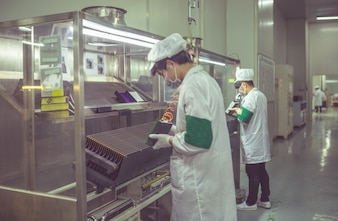 Employees in protective clothing work in clean factories
