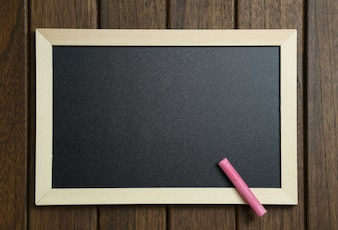 Empty blackboard with chalks on vintage wooden background