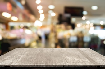 Empty wood table over blurred shopping mall / department store background