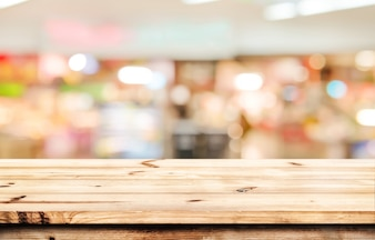Empty wood table ready for your product display montage. Lights bokeh blurred supermarket background