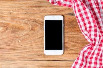 空の木製テーブルと布赤いナプキン、携帯電話