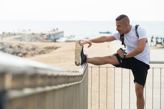Energetic young athlete stretching with railing