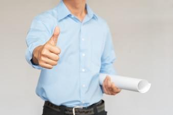 エンジニアが青写真と親指を持って