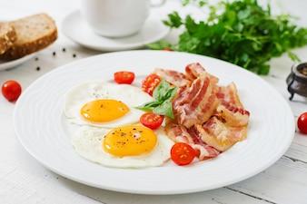英語の朝食 - 揚げた卵、トマト、ベーコン。