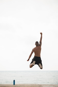 Enthusiastic sporty man jumping on shore