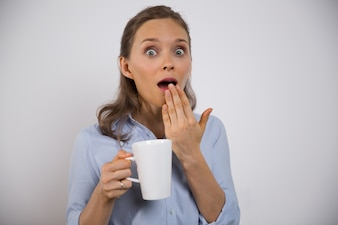 Excited businesswoman with mug shocked with news