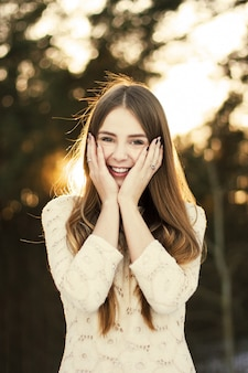 Excited girl with hands on face