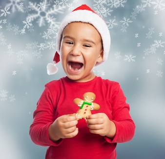 Excited young boy celebrating christmas with a gingerbread