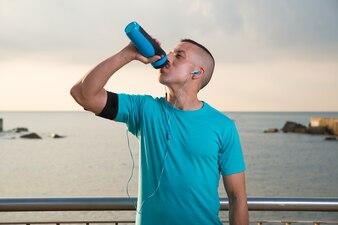Исчерпанный мужской спортсмен питьевой воды на открытом воздухе