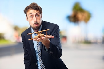 Expressive executive with a wooden plane on hand