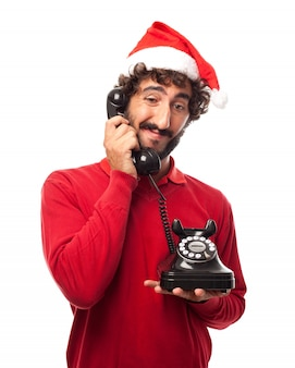 Expressive guy with santa hat holding an old phone