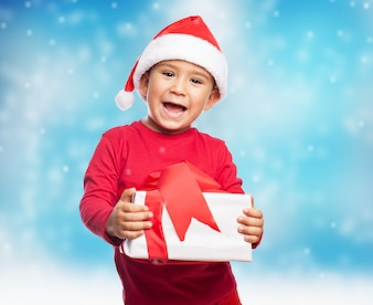 Expressive little boy with present and santa hat