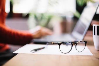 Eyeglasses in desktop of worker