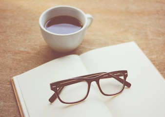 Eyeglasses on notebook and black coffee, retro filter effect