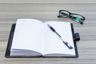 Eyewear, pen and opened diary on desk
