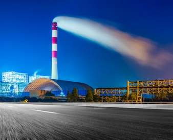 Factory With Smoke Stack Against Sky At Night