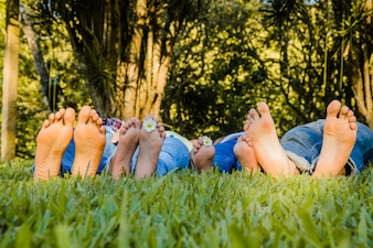 Family lying barefoot on the grass