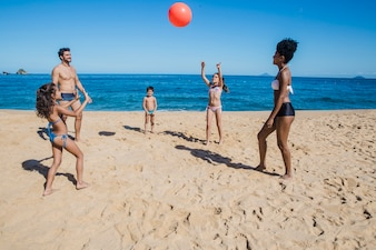 Family playing volley on the beach