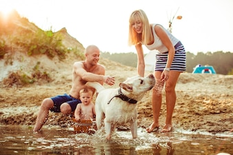 Family relaxing on shore with dog