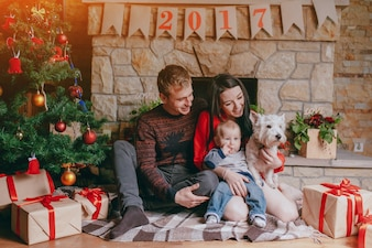Family sitting in front of the fireplace with their baby and their dog and a christmas tree