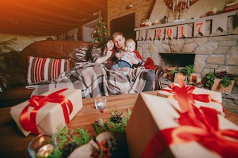 Family sitting on a couch seen through brown gifts with red ribbons