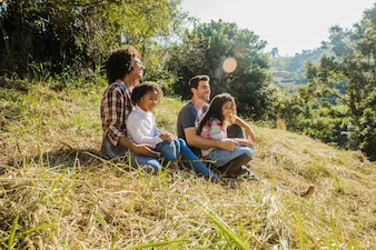 Family sitting on a sunny hill