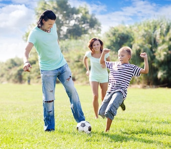 Family with teenager child  playing with soccer ball