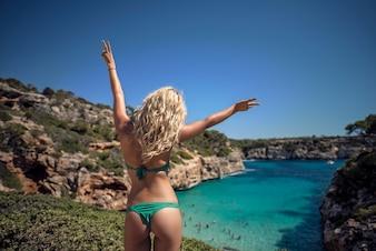 海岸、熱帯の島でポーズをとっている緑色のビキニの金髪のセクシーな美しい少女のファッション写真