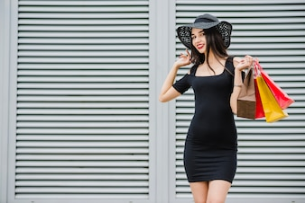 Fashionable girl holding shopping bags smiling