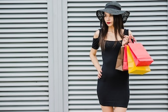 Fashionable girl holding shopping bags standing