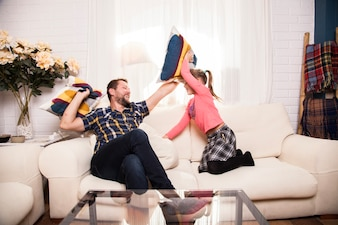 Father and daughter having fun with cushions