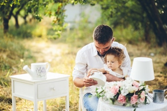 Father and daughter sitting on a white chair in the field