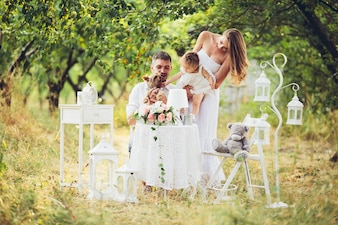 Father and mother with their daughter in the middle of the field with white table and chairs