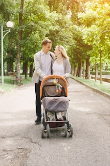 Father and young mother walking her baby by the park in a cart