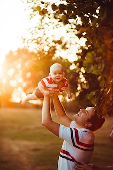 Father holds his little son up standing in the rays of evening s