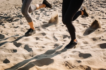 Feet view of woman jogging on sand