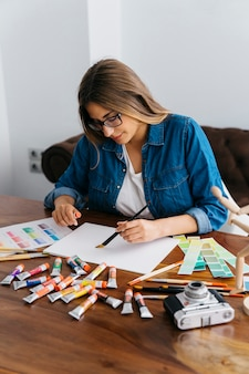 Female artist painting at desk
