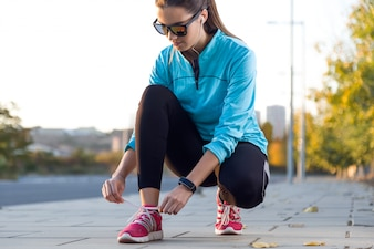 Female athlete tying laces for jogging.