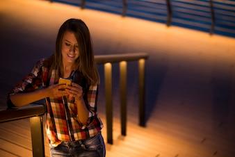 彼女の顔のスクリーンライト、空のスクリーン電話に反映された携帯電話でテキストメッセージを読む女性の白人学生