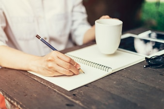 Female hand with pencil writing on notebook. Woman hand with pencil writing on notebook at coffee shop.