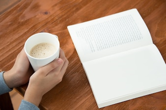 Женские руки с чашкой кофе на столе с книгой