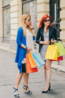 Female shoppers with bags on street