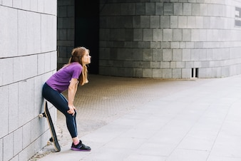 Female skateboarder rests against brick wall