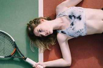 Female tennis player lying on ground