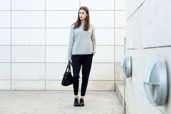 Female wearing knitted sweater standing in city.