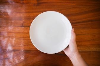 女性(女性)の手は、木製のテーブルの上に白い皿(プレート)を持っています。