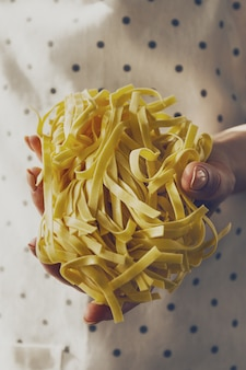 Feminine hands cook holding tasty fresh raw traditional italian pasta. Closeup. Toning.